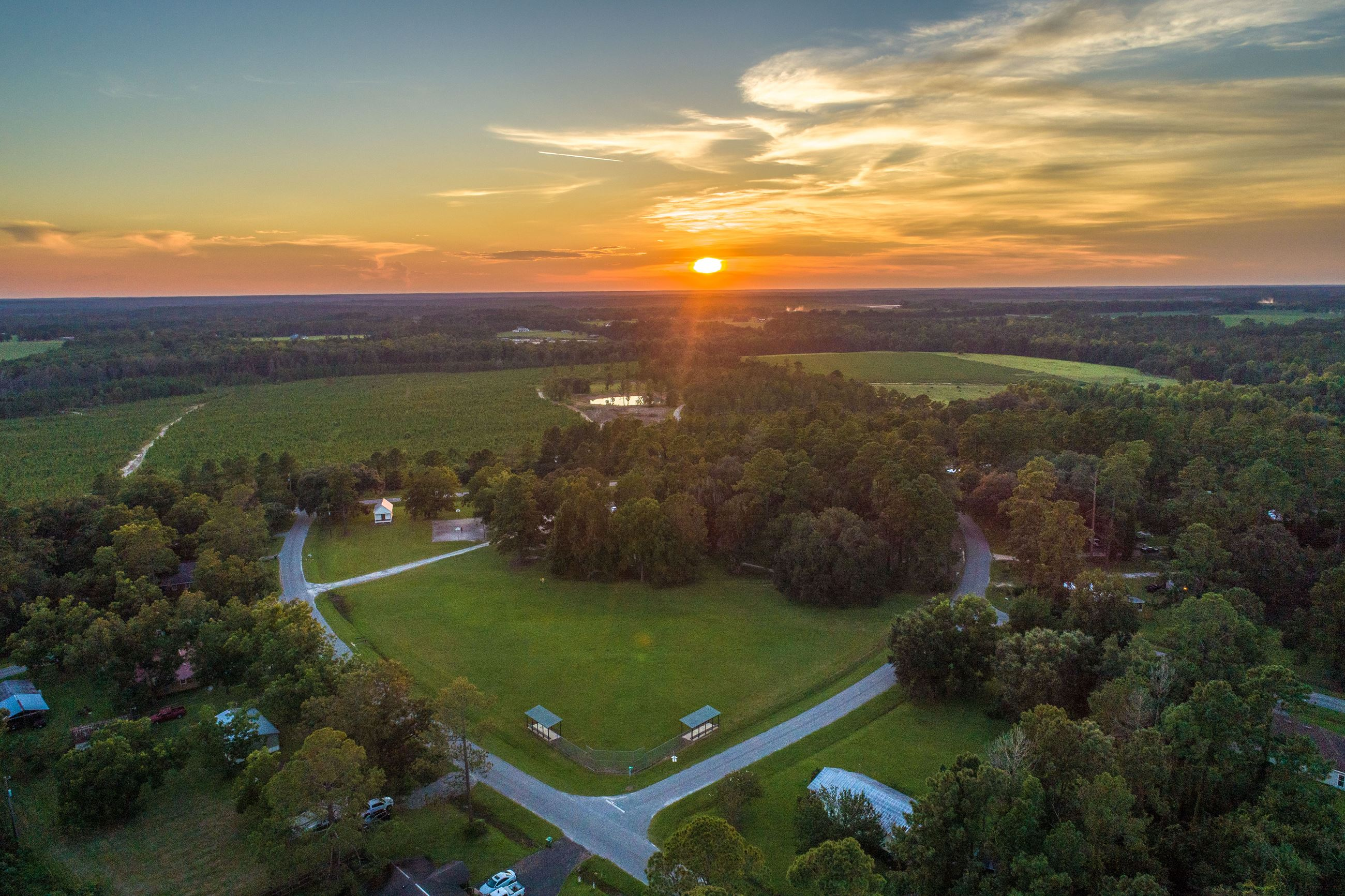 An image of an aerial view of park with trees an open fields and the sunset in the distance.