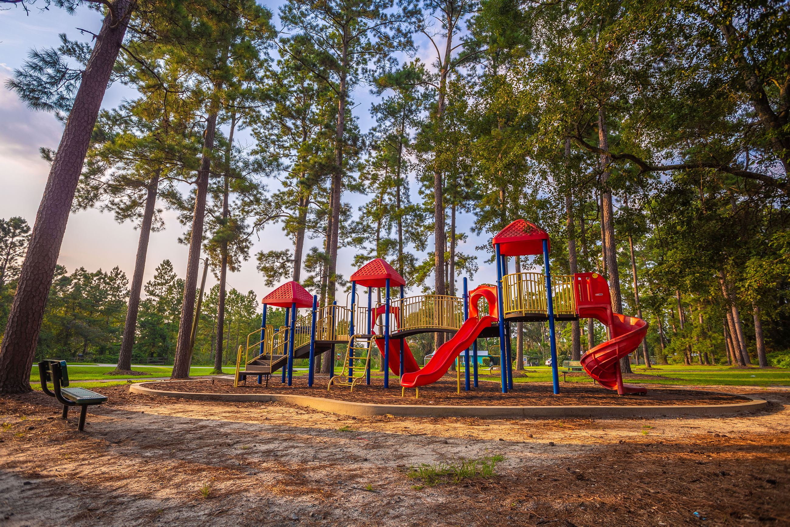 An image of a red playground structure with slides and monkey bars for children.