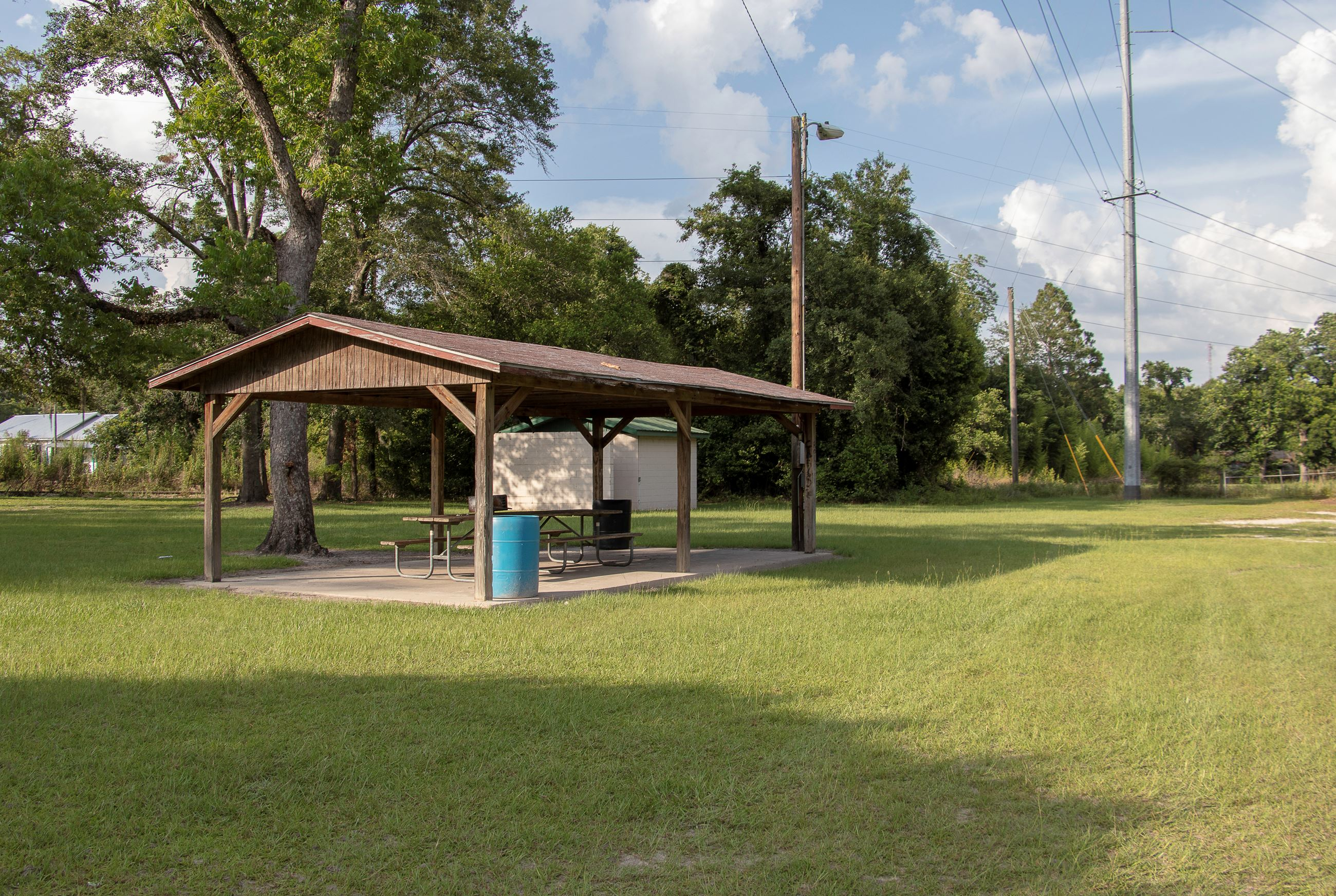 An image of an brown picnic shelter in a park.