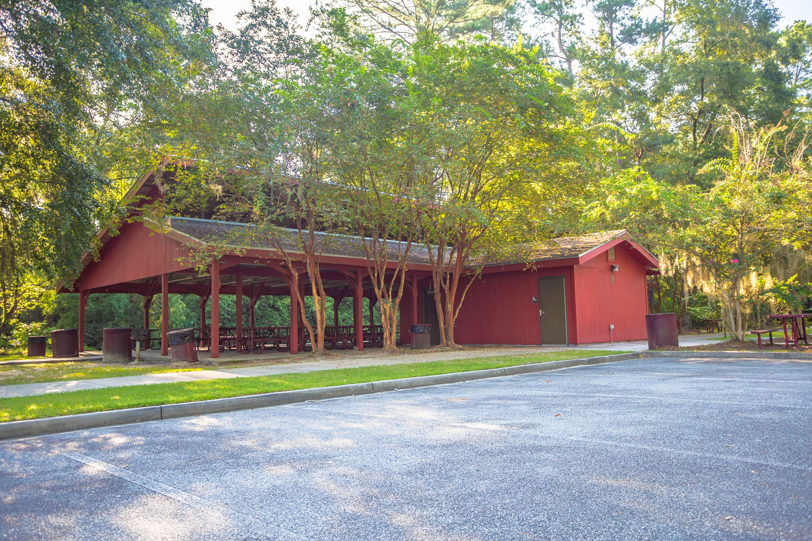 An image of a large red picnic shelter that can hold over 100 people surrounded by trees.