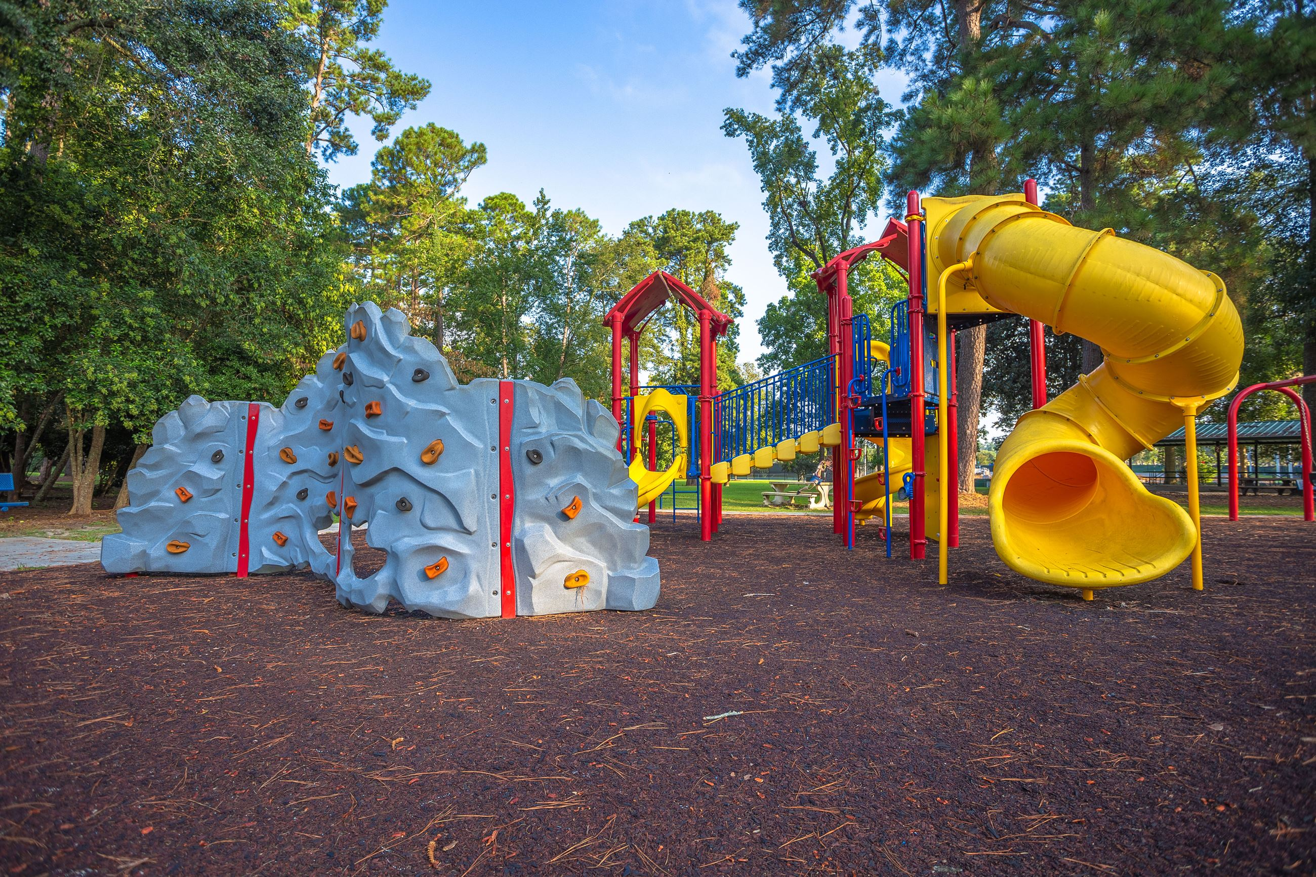 An image of a playground with a rock wall and a yellow slide.