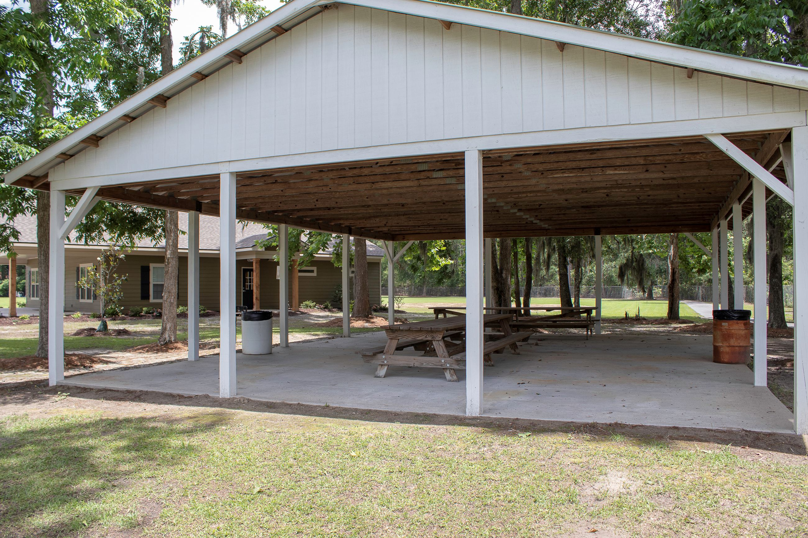 An image of a white picnic shelter with several picnic tables.