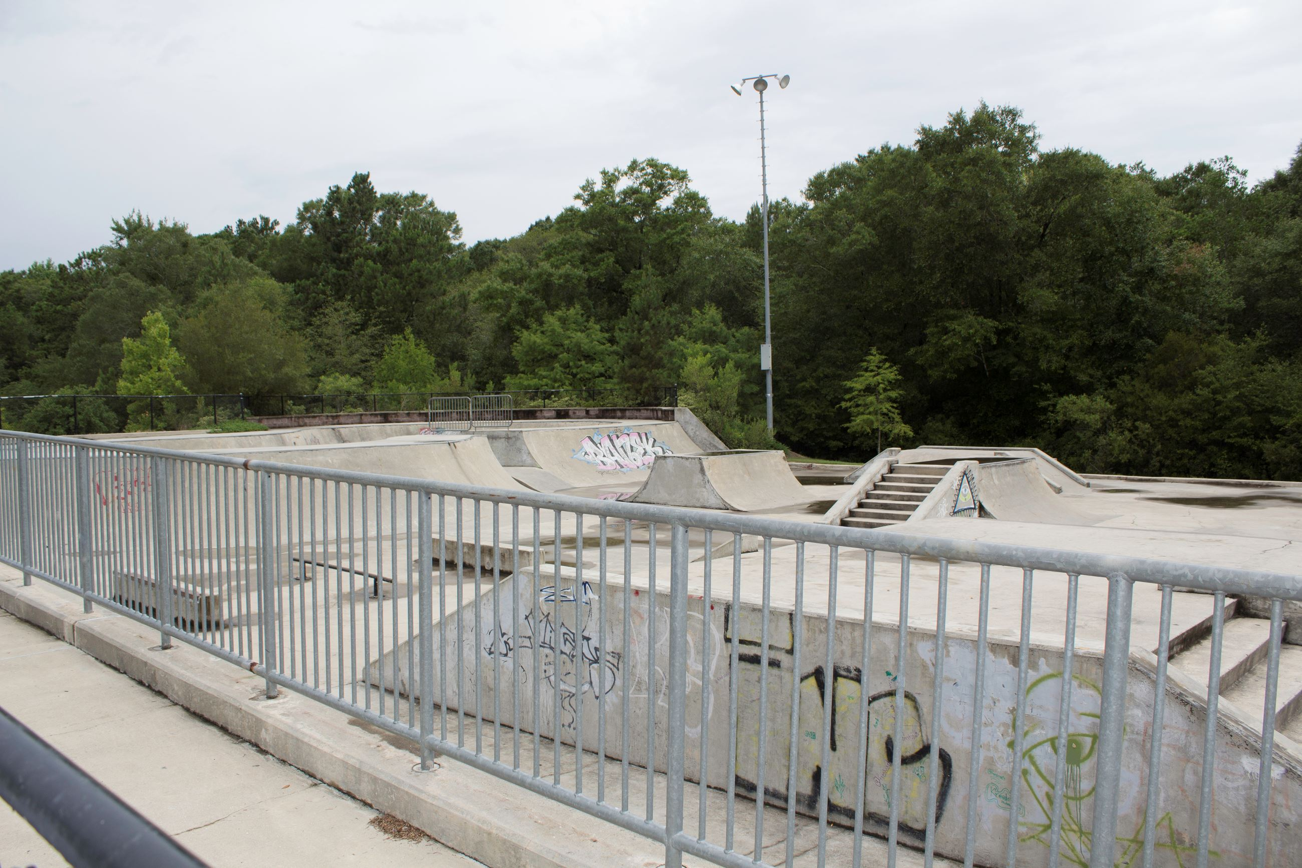 An image of a railing overlooking a concrete skate park.