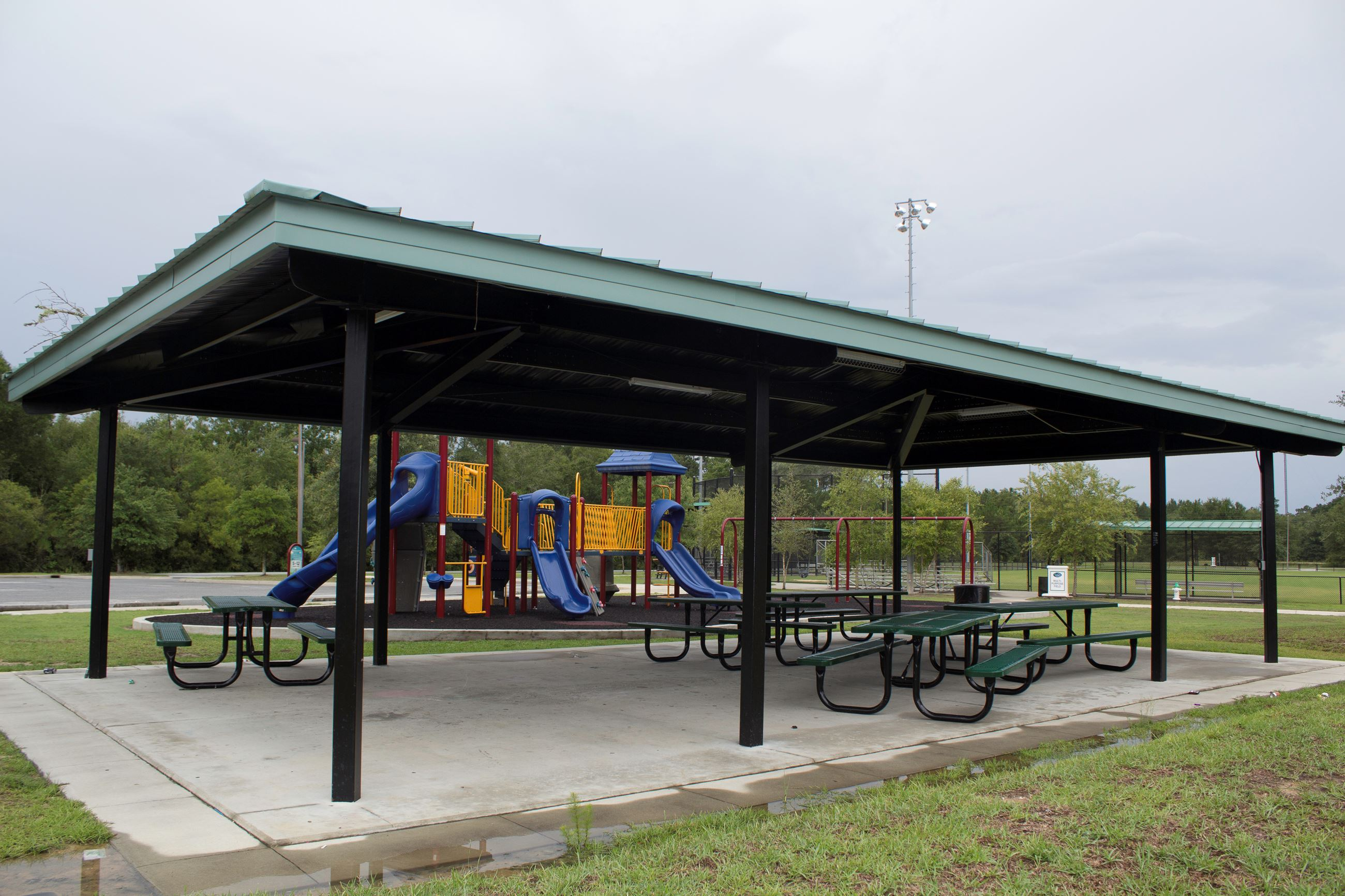 An image of a picnic shelter with a playground behind it.