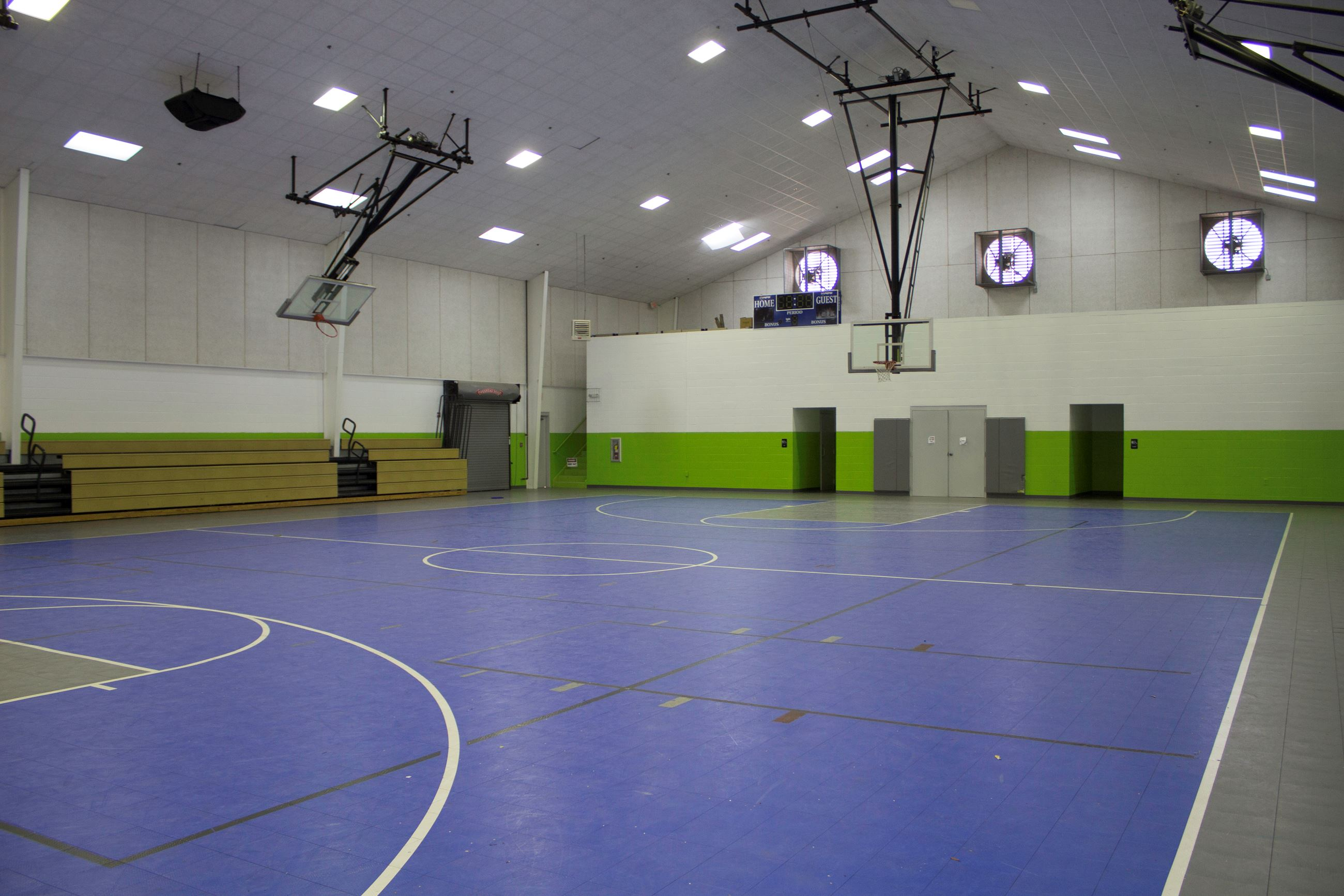 An image of a gymnasium with blue basketball court.