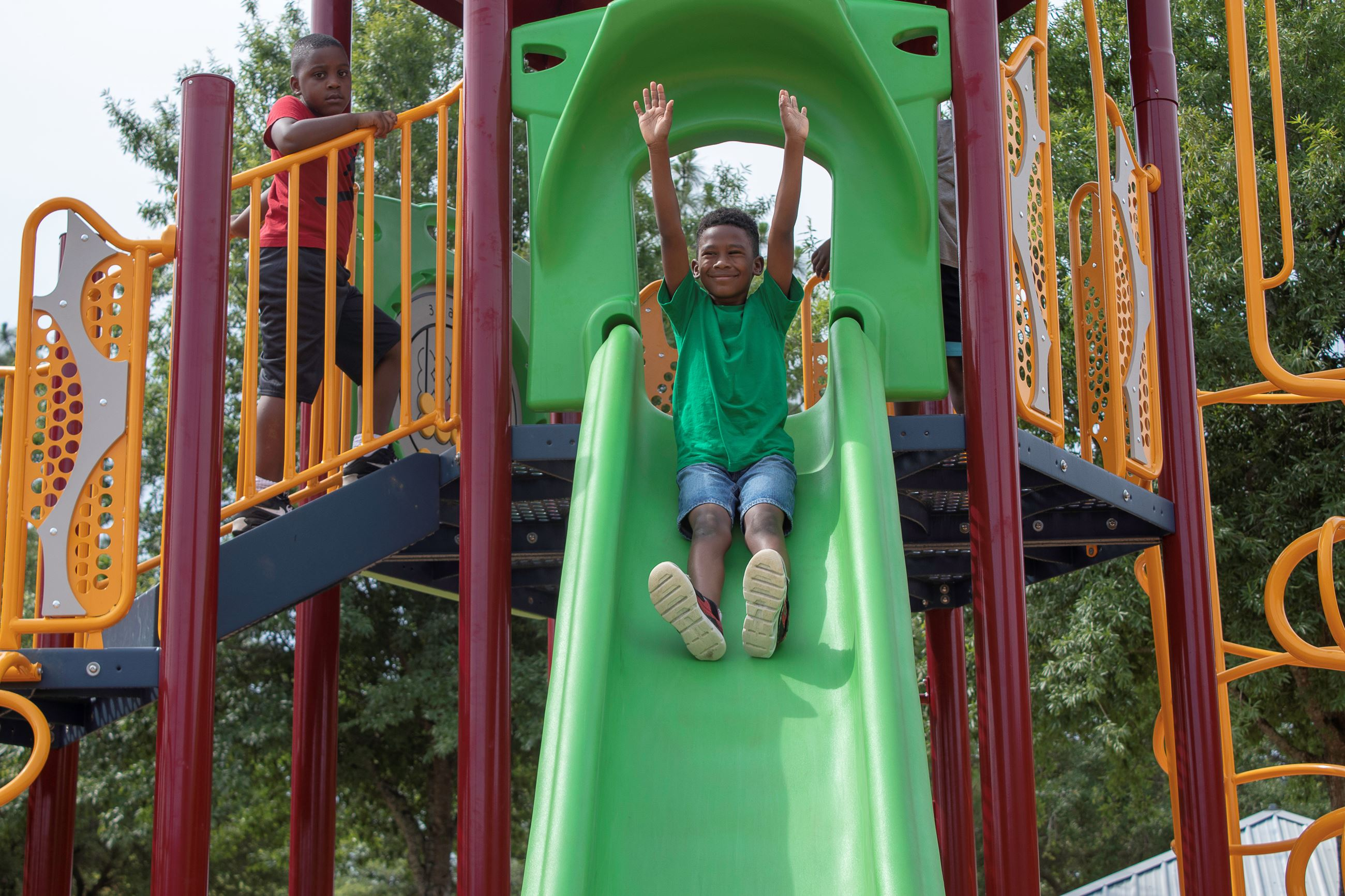 An image of a child sliding down a green slide.