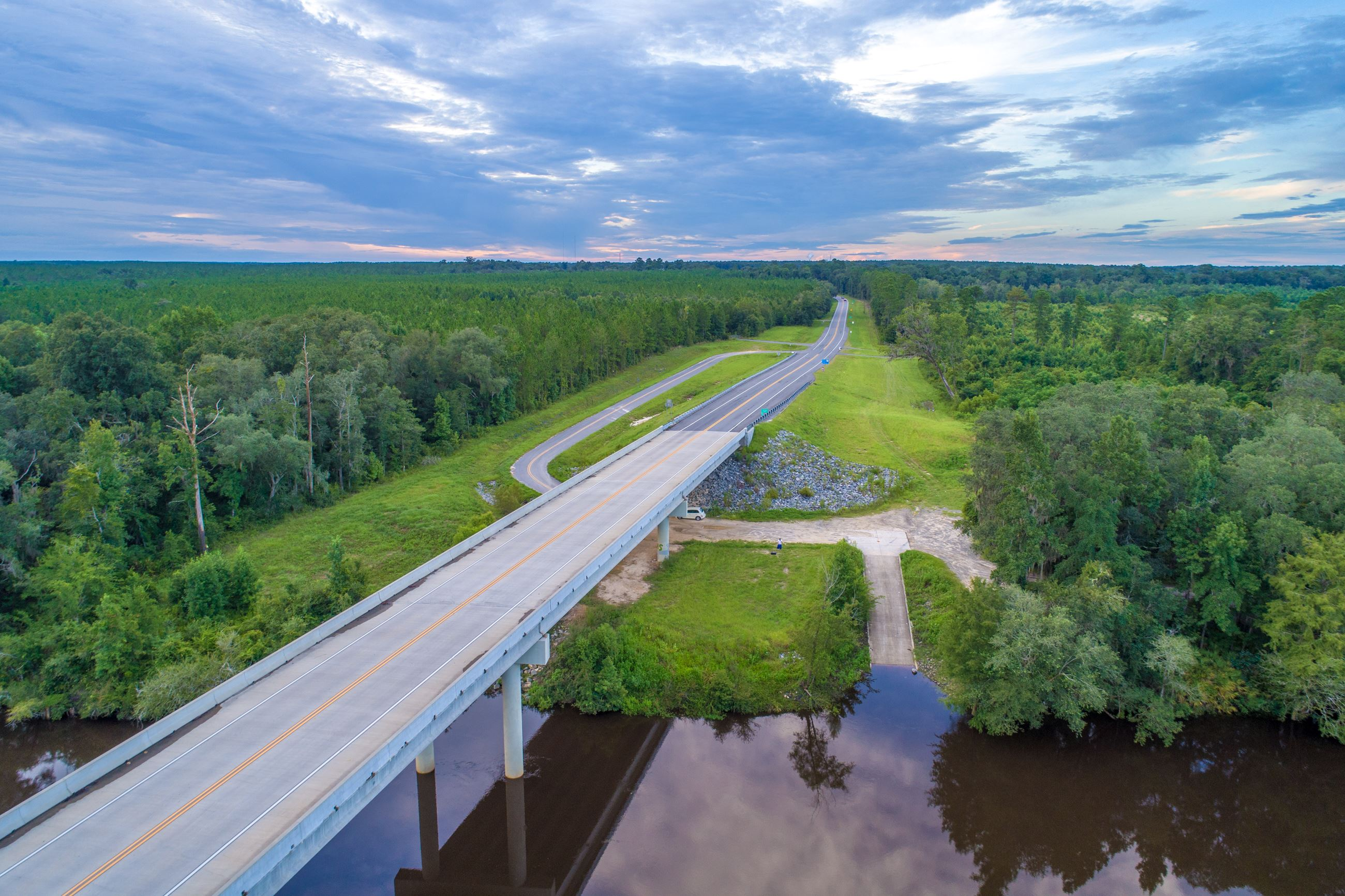 Image of an aerial view of a boat ramp into a river next to a highway.