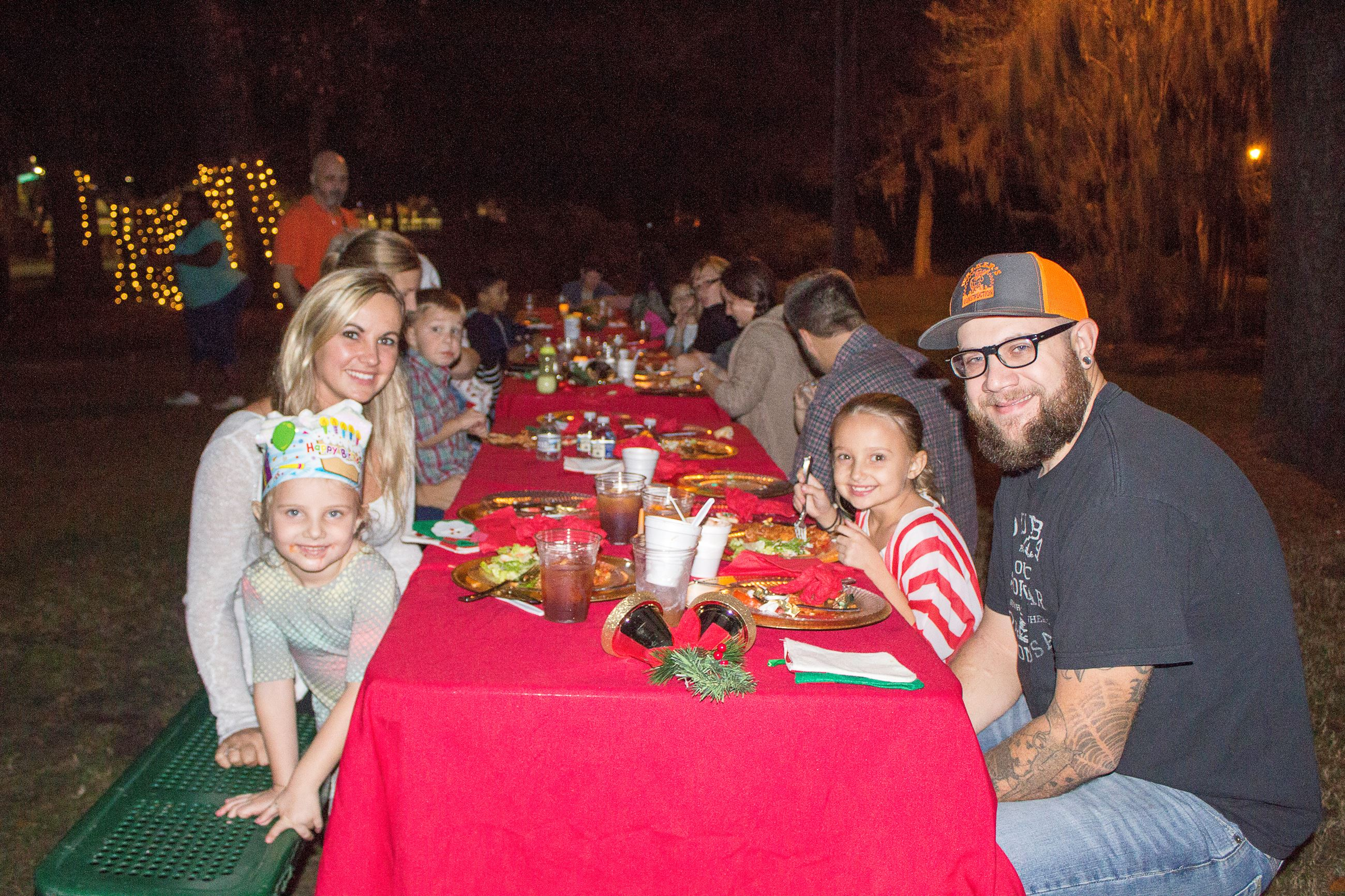 Image of a family at a table in the park.