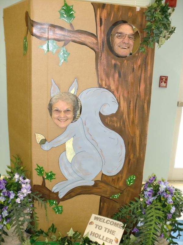 Man and woman pose at squirrel and tree cutout photo opp