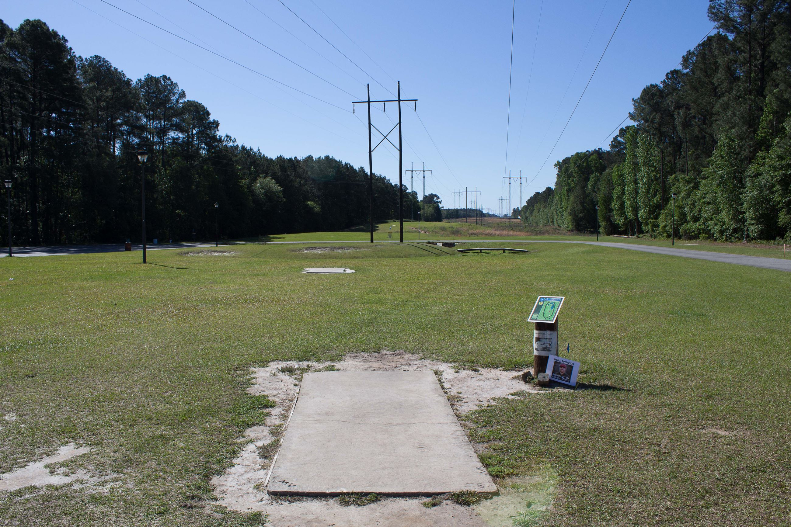 An image of an tee box for a disc golf hole at a park.