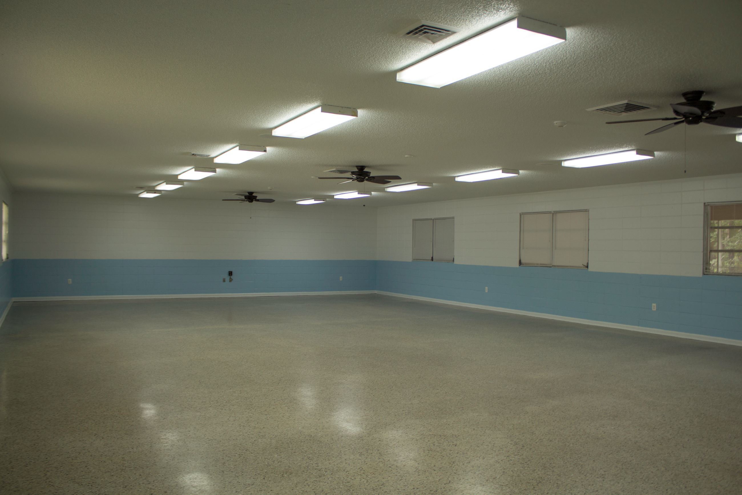 An image of a large multipurpose room with white and blue walls and fluorescent lighting.