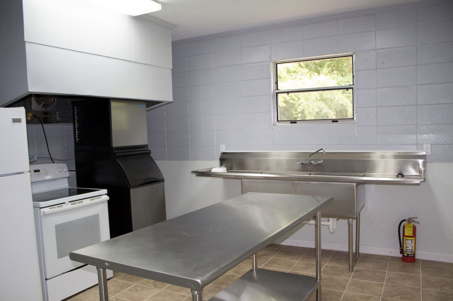 An image of a kitchen with a large stainless steel industrial sink and stainless steel table.
