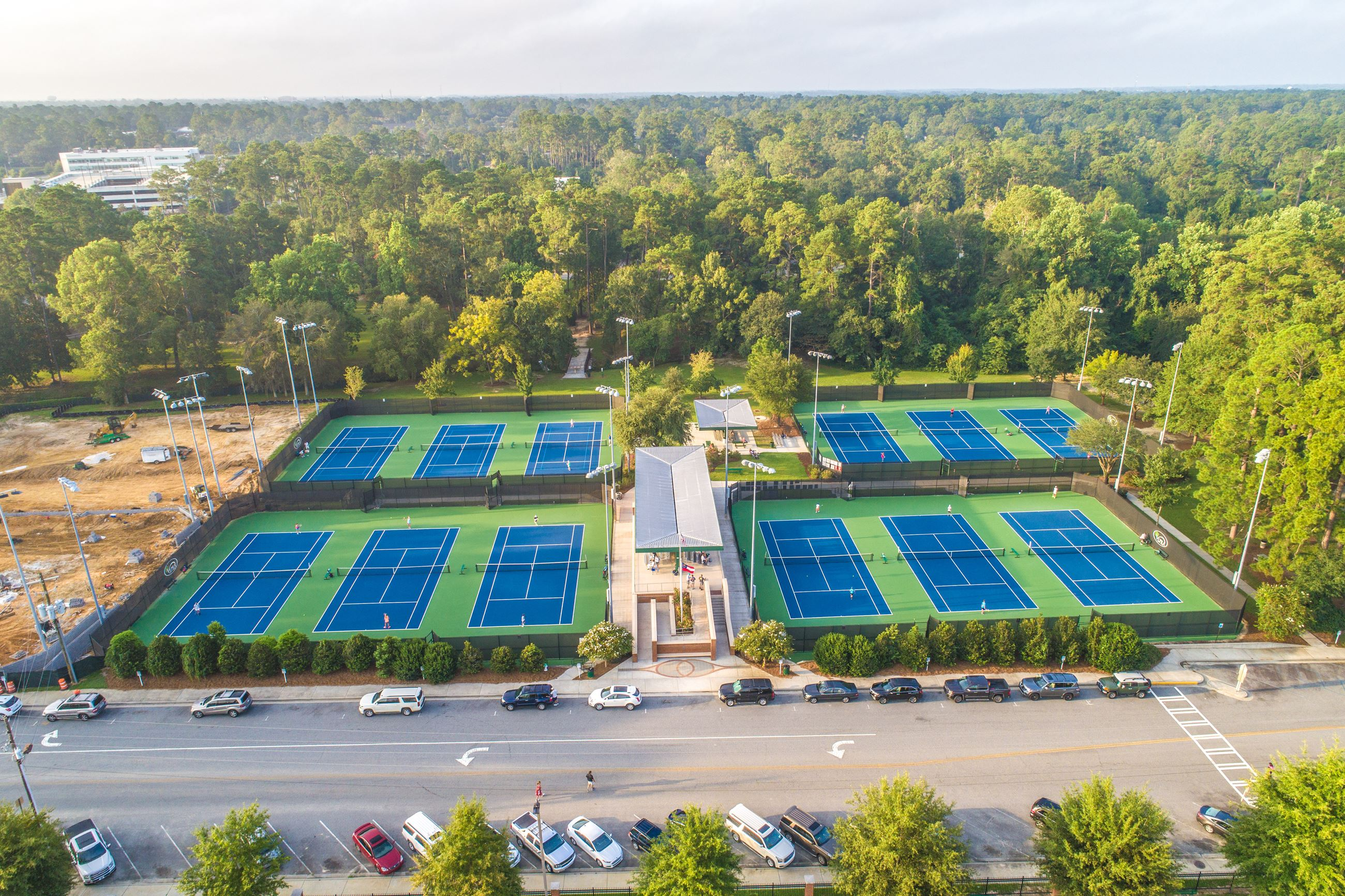 An image of an aerial view of tennis complex with eight blue courts on a green background.