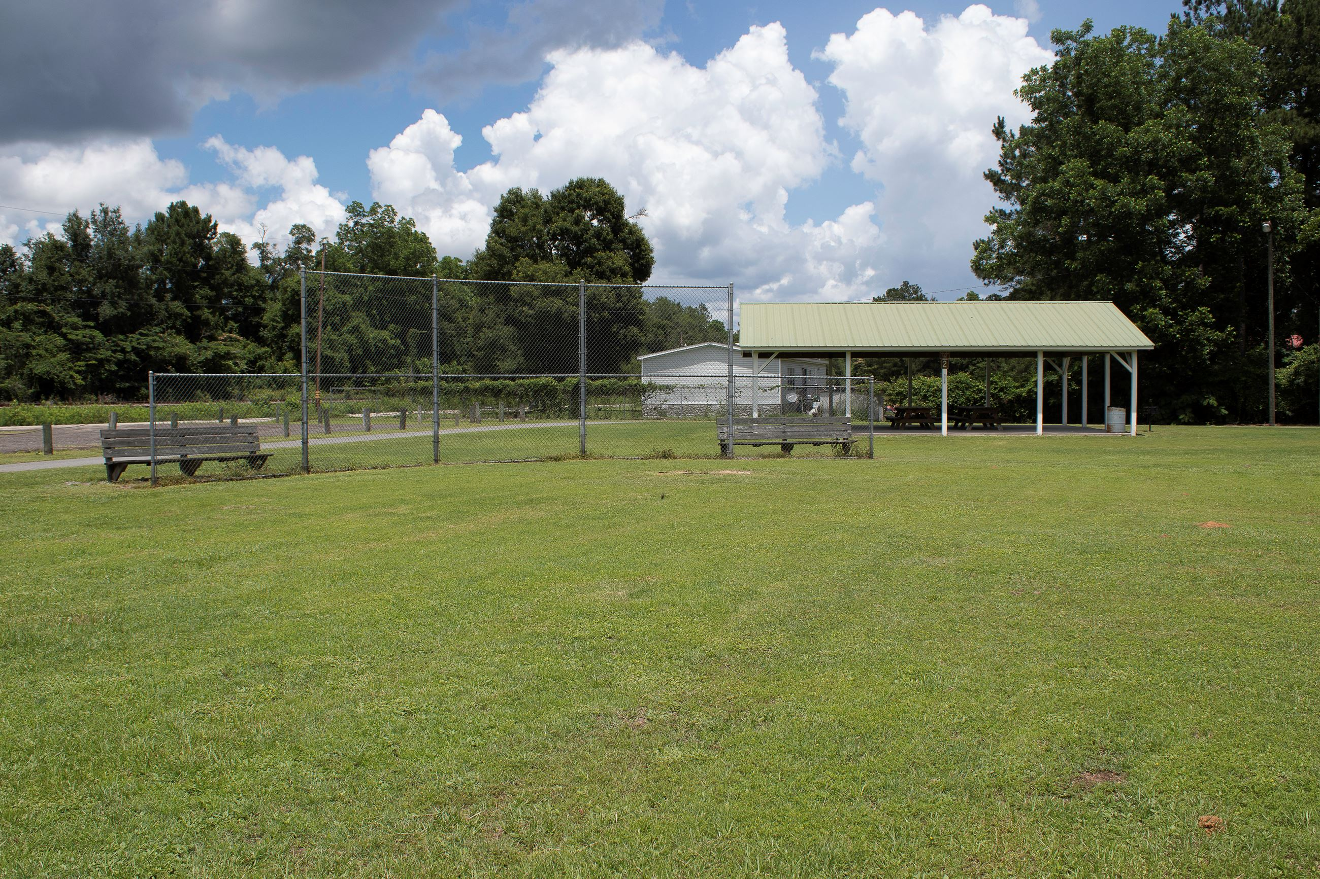An image of a grassy field with a baseball backstop and a white picnic shelter behind them.