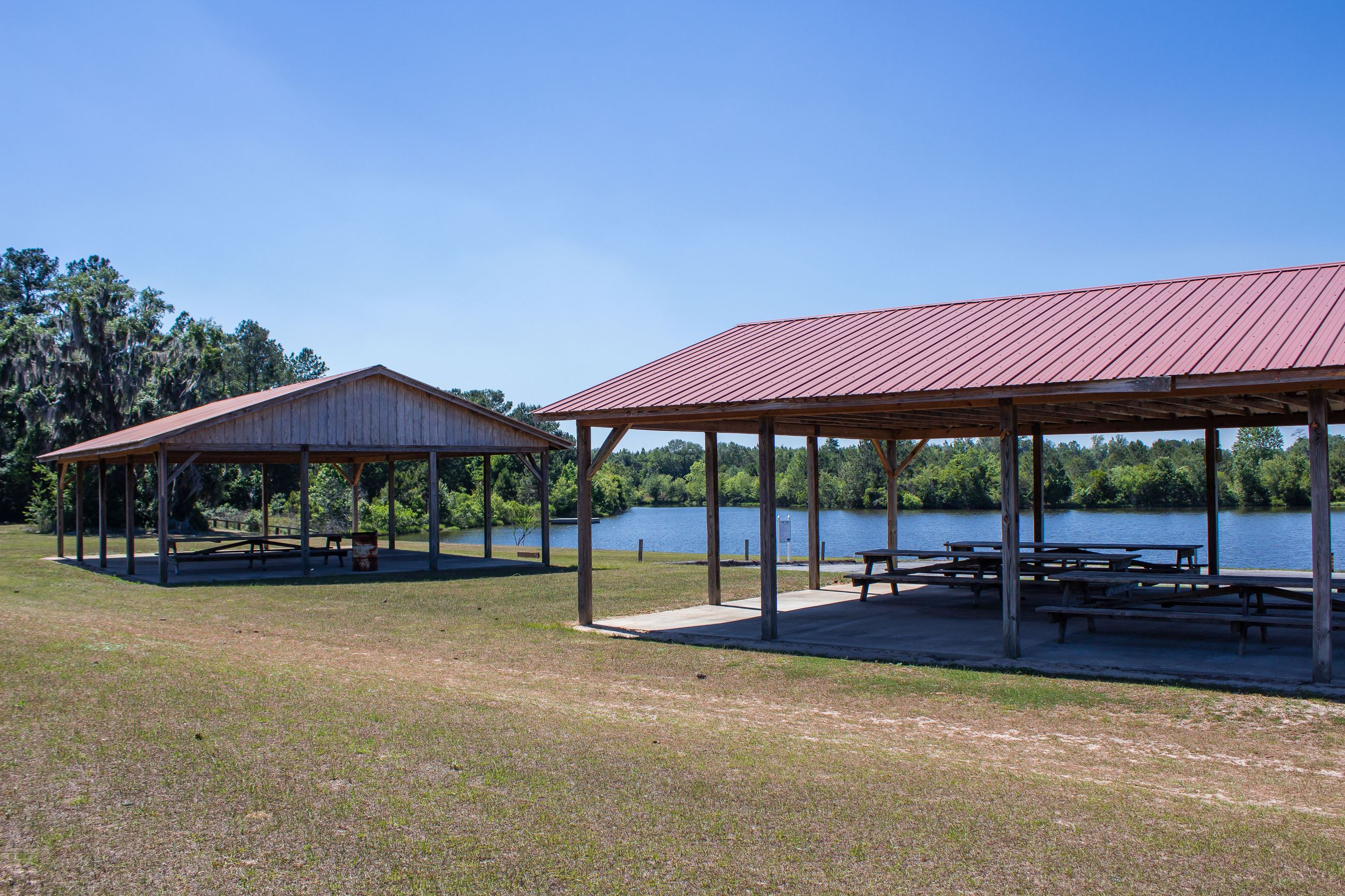 An image of two picnic shelters at a park with a lake in the background.