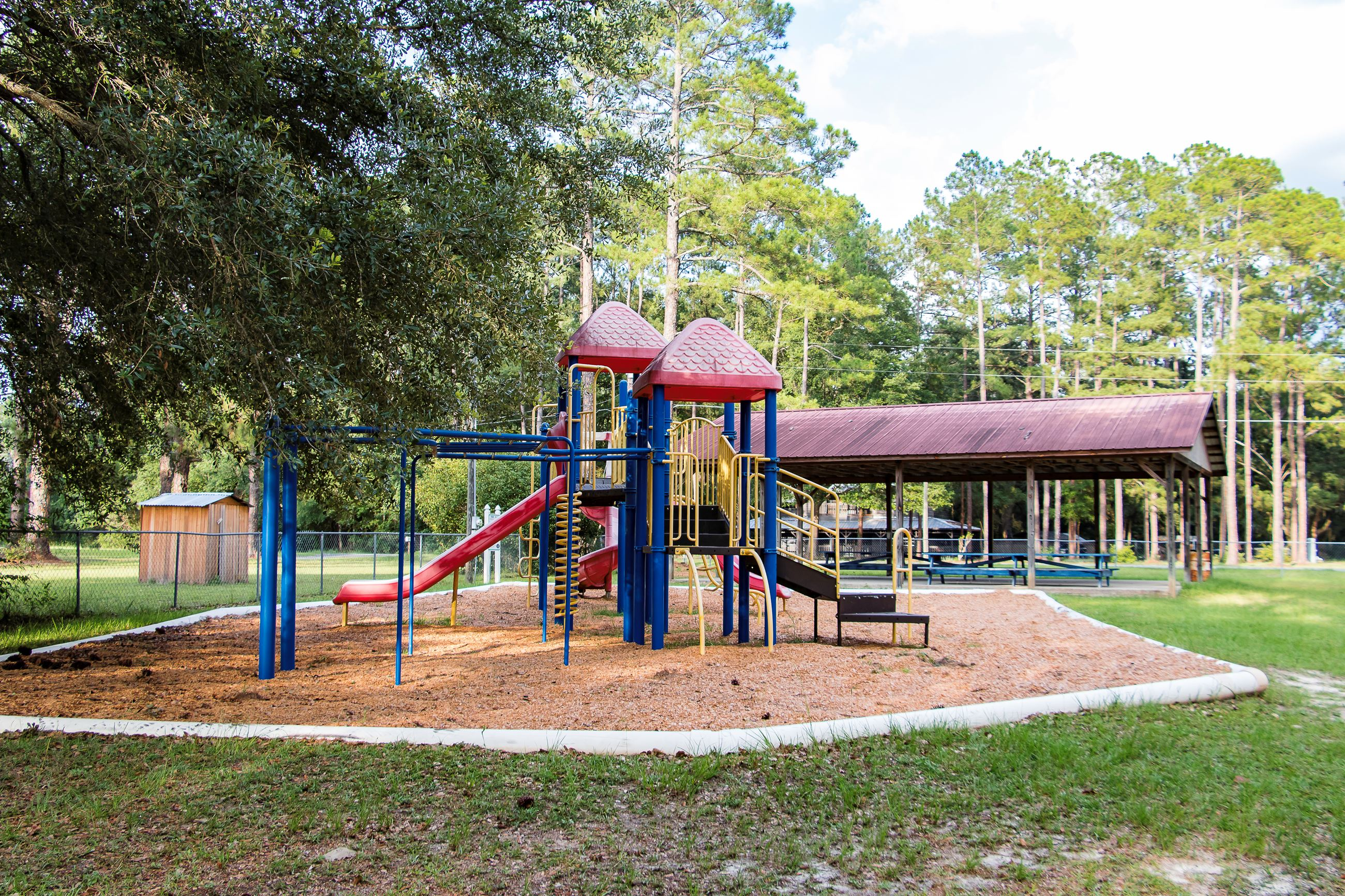 An image of a playground with a picnic shelter in the background.