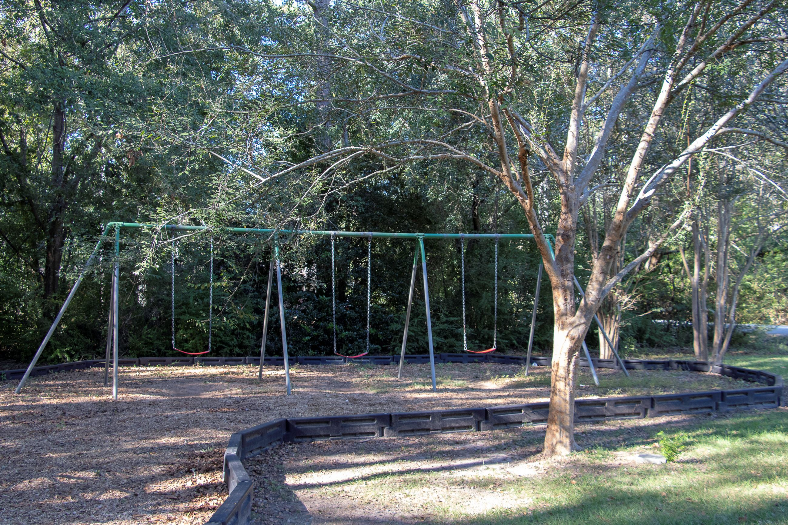 An image of a swing set in a park.