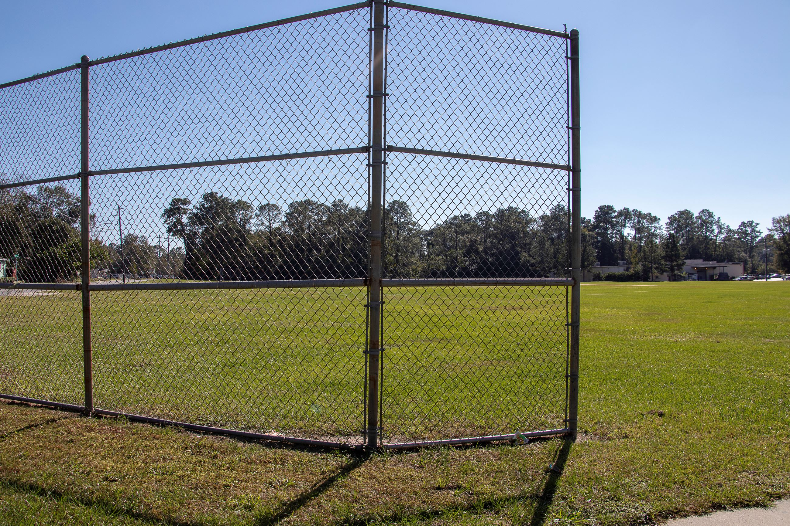 An image of a baseball backstop at a large field.