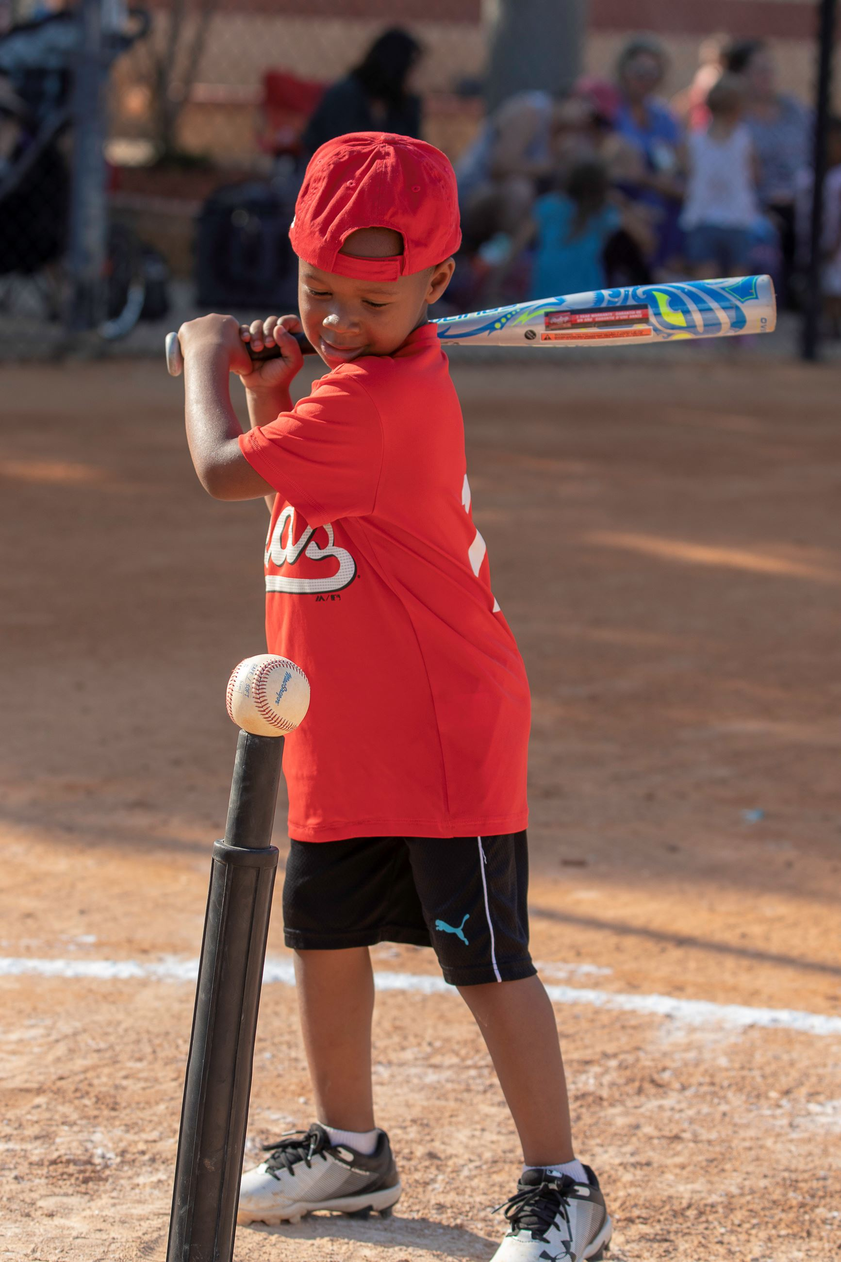 Image of little boy batting at tee ball.