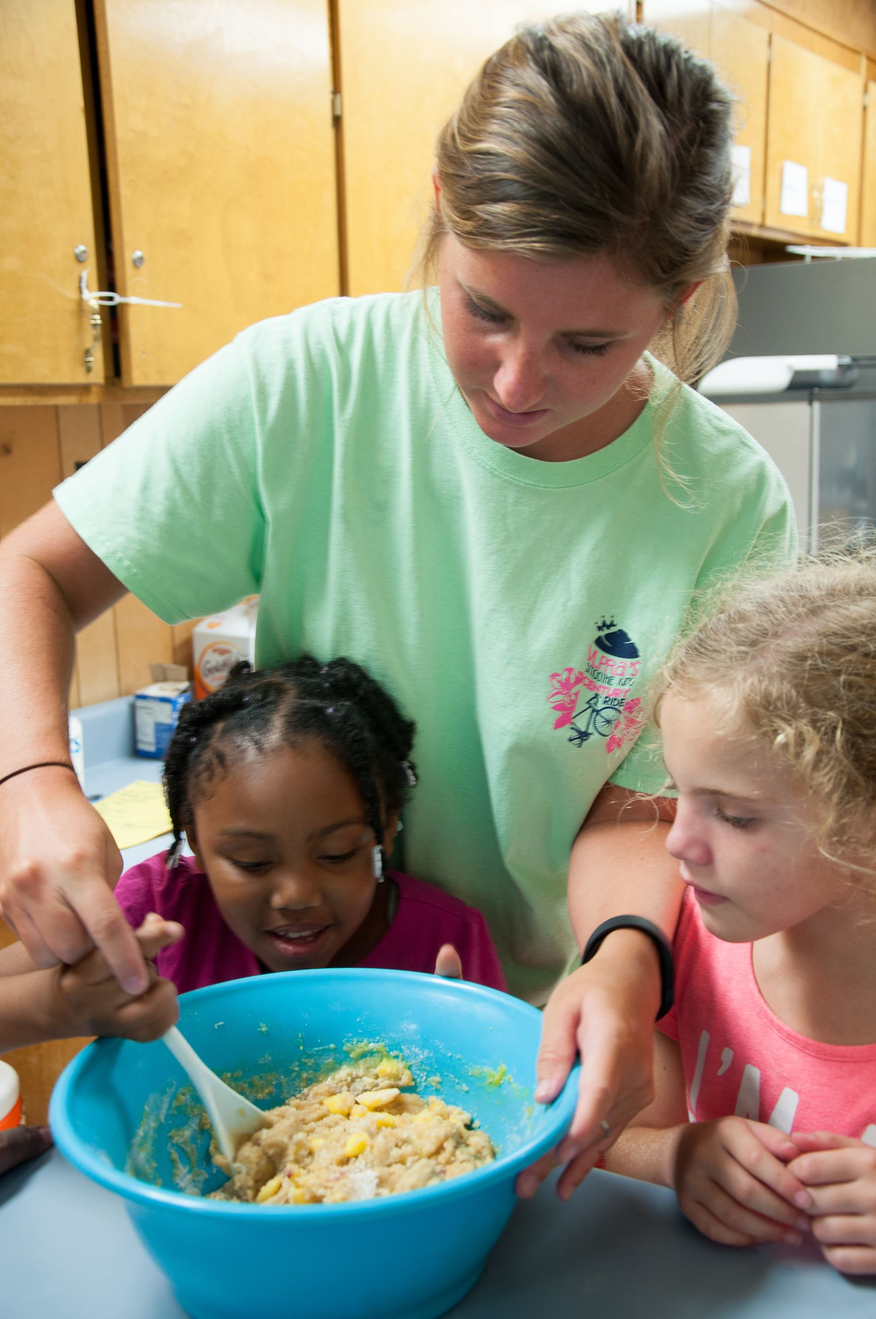 An image of a woman helping a little girl stir a bowl of batter.