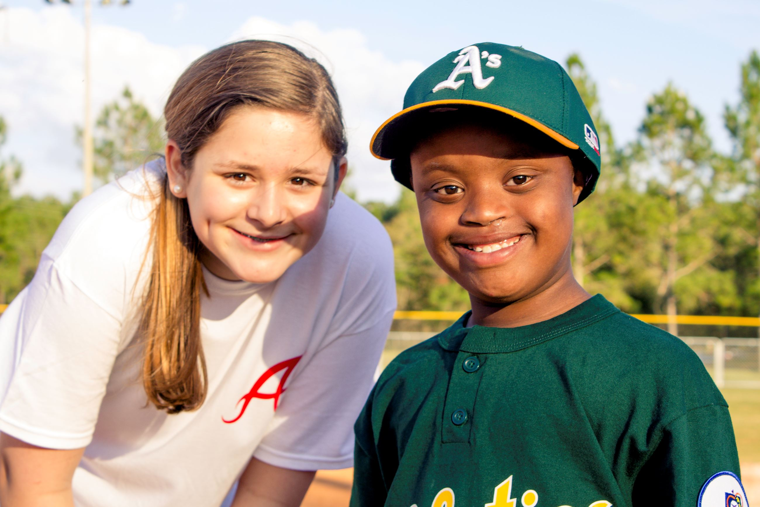 Image of a Miracle League Baseball player with his buddy.