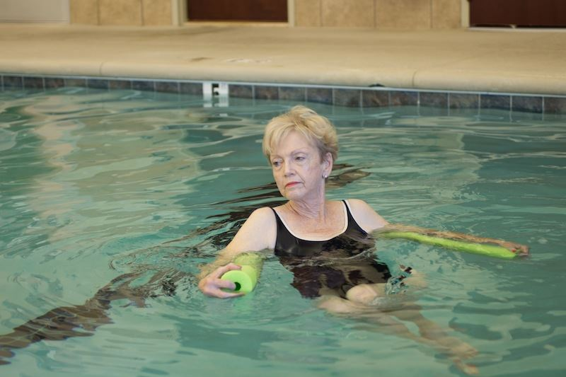 Woman in pool with noodle